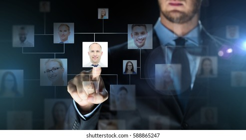 business, people, employment, technology and network concept - close up of businessman in suit touching virtual screen with contact icons over dark background