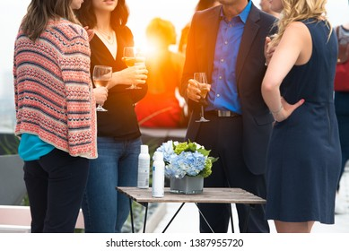 Business people enjoy drinks and conversation on the event on city rooftop