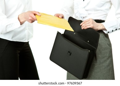Business people exchanging documents; closeup of businesswomen's hands holding envelope/document/file; isolated on white background