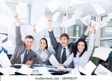 business people excited happy smile, throw papers, documents fly in air, businesspeople sitting at office desk hold hands arms up, success team concept after sign contract