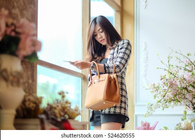 Business people, executives, a beautiful girl poses with a commitment to stand with the women fashion handbags.,Lighting with sun flare