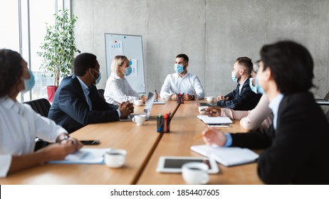 Business People In Face Masks Sitting At Desk During Corporate Meeting In Modern Office. Coworkers Safety, Virus Protection At Workplace Concept. Entrepreneurship And Covid-19 Coronavirus Pandemic