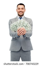 business, people and finances concept - smiling businessman with american dollar money