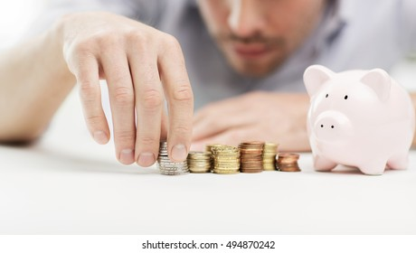 business, people, finances and money saving concept - close up of businessman with piggy bank and coins