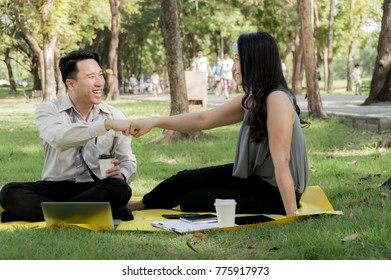 Business people fist bump into each other because they business do it together success Is on target While the rest of the park is shady. With blurred soft nature background.