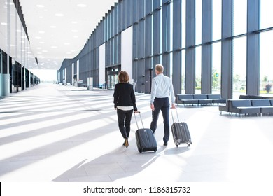 Business people in formal clothing walking with wheeled bags at airport terminal