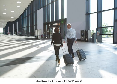Business people in formal clothing walking in airport terminal with suitcases