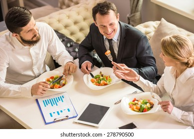 Business people in formalwear discussing something during business lunch.