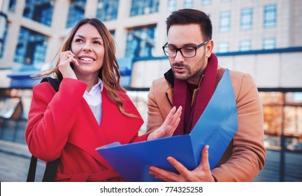 Business people in front of the corporation. Businesswoman talking on a mobile phone while her colege watching documents in folder. Business, education, lifestyle concept