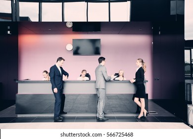 Business people at front desk reception of hotel or airport