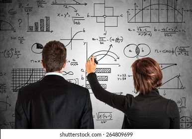 Business people in front of math formulas