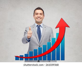 business, people, gesture and success concept - happy smiling businessman in suit with growing chart showing thumbs up over gray background