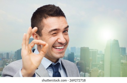 business, people, gesture and success concept - happy smiling businessman in suit showing ok hand sign over city background