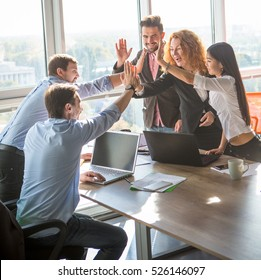Business people giving five to their colleague after dealing with foreign partners and signing contract or agreement between companies, enterprises or firms. Teamwork concept.