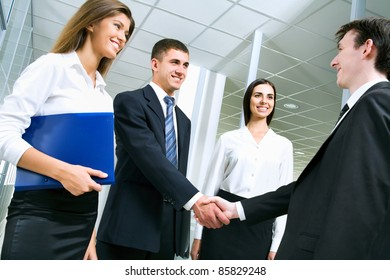 Business people greet each other in the lobby of the office