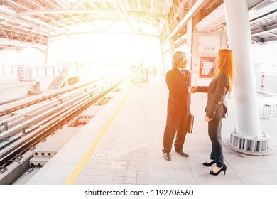 Business people to greet and welcome another business person on train platform