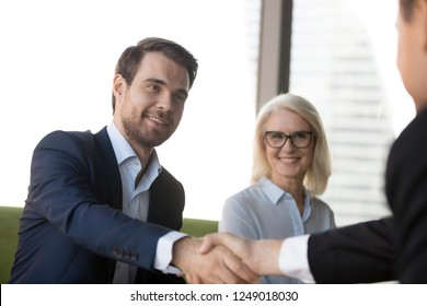 Business people greeting each other at meeting, focus on handsome young confident businessman welcoming client. Aged female in eyeglasses, team leader and company partner handshaking in modern office