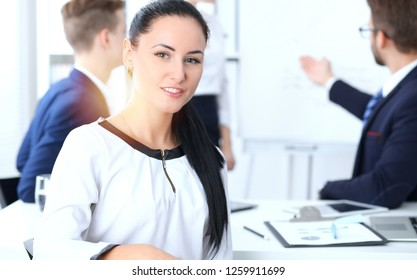 Business People group at meeting in office. Focus at beautiful cheerful smiling businesswoman. Conference, corporate training or brainstorming of team. Success and  negotiation concept