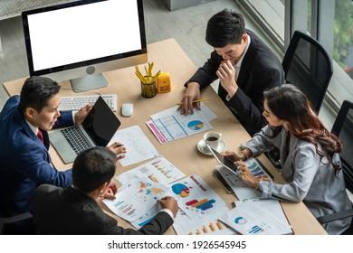 Gruppentreffen für Geschäftsleute wurde von der Top-Ansicht im Büro aufgenommen. Professionelle Geschäftsfrauen, Geschäftsleute und Büroangestellte, die in Teamkonferenzen mit Projektplanungsdokument am Sitzungtisch arbeiten.