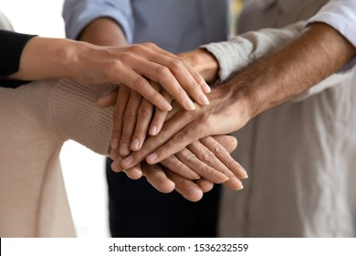 Business people group stacking hands together in pile building strong reliable responsible dream team helping in teamwork, corporate partnership support, company staff unity concept, close up view