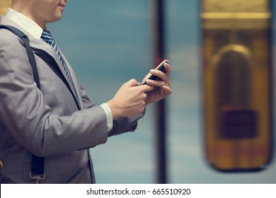 Business people hand using smart phone in subway station, train passing by at the background.