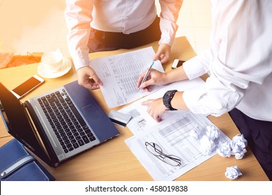 Business people hands  writing payment document  while discussing it with laptop on wood desk, vintage Tone