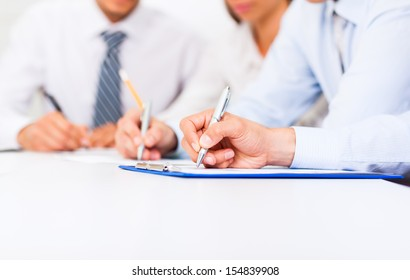 Business people hands writing sign up contract, sitting at desk office write notes. Close up paper signing a business contract, businesspeople holding pens seminar