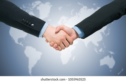 Business people handshake in front of a world map. Blue toned