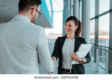 Business people handshake near the office building windows.