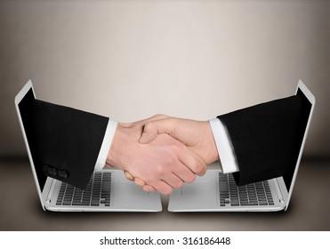 Business people handshake through computer