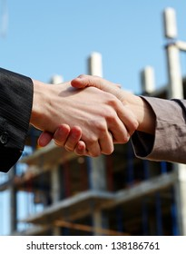 Business people handshaking while new building