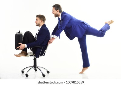 Business people have fun and ride on office chair. Businessman pushing male colleague in chair on white background. Coworkers with cheerful faces enjoy time together. Funny business, success concept.