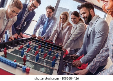 Business people having great time together.Colleagues playing table football in modern office.