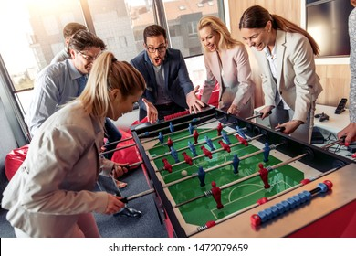 Business people having great time together. Colleagues playing table football in modern office.