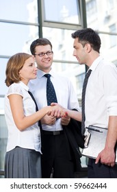 Business people having a handshaking in front of office building. Young people communicating and trying to get consensus outdoors.