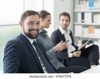 Business people having a meeting in the office and discussing together, a man is smiling and looking at camera in the foreground