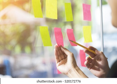business people having a meeting in office, business people post it notes in glass wall, soft focus