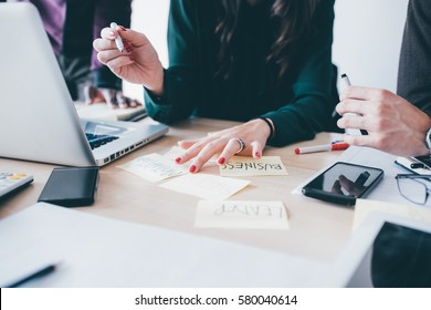 Business people having a meeting in office. They are sitting at work desk with post it notes, writing and discussing - business, teamwork, brainstorming concept