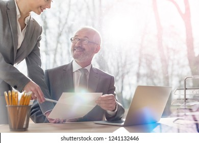 Business people having a team meeting. in the office business man smiling at woman at his desk