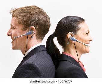 Business people in headsets standing back to back