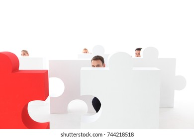 Business people hiding behind puzzle pices isolated on white background
