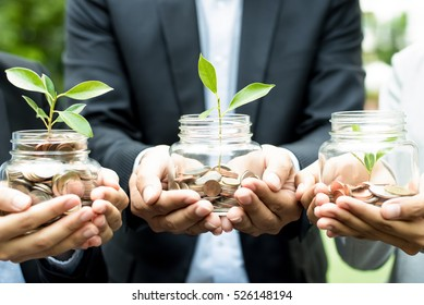 Business people holding glass jars with plants growing from money - investment and financial metaphor