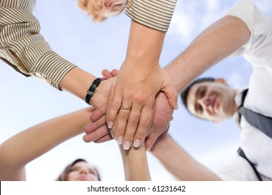 Business people holding hands all together across the blue sky. Office workers showing unity, success and team work in their international company, firm or enterprise.