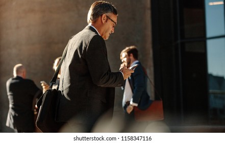 Business people in hurry to reach office using mobile phone while walking on city street. People commuting to office in the morning carrying office bags busy with their mobile phones.
