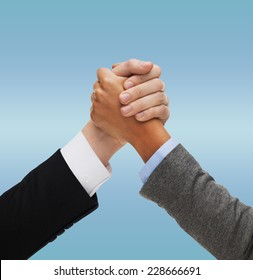 business, people, international and competition concept - close up of two hands multiracial armwrestling or handshake over blue background