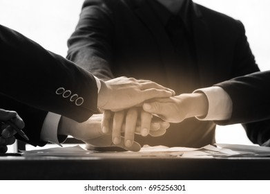 Business people join hands power teamwork the goal success together. with black and white picture