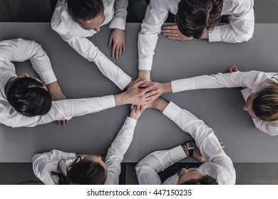 Business people joining hands in stack sitting around the table