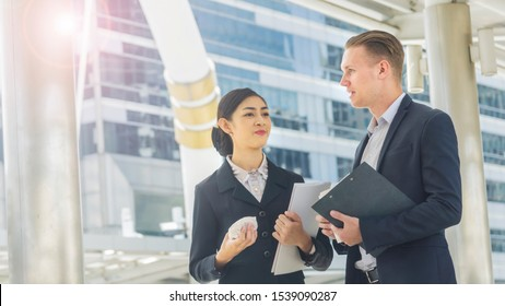 business people lady with hamburger breakfast in hands and caucasian man talk together with feeling happy