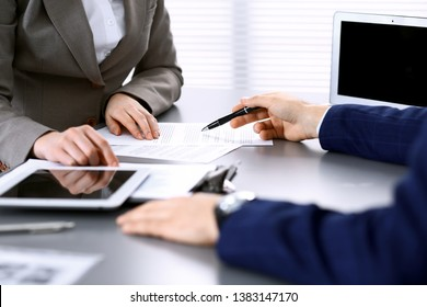 Business people and lawyer discussing contract papers sitting at the table, hands close-up. Teamwork or group operations concept