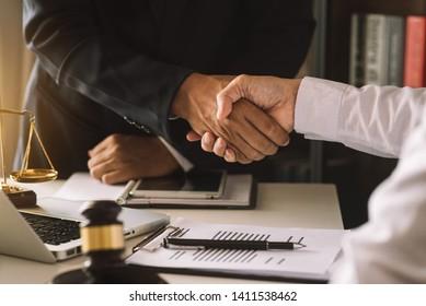 Geschäftsleute und Rechtsanwälte, die Vertragsunterlagen erörtern, die am Tisch sitzen. Rechtskonzepte, Beratung, Rechtsberatung. Morgenlicht